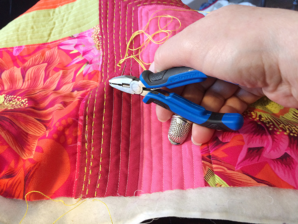 Using pliers to push needle through quilt